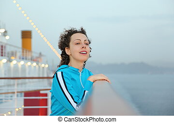 beautiful woman wearing sportsuit is standing on deck of cruised ship and looking away