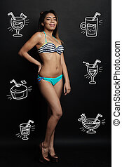 Beautiful woman wearing swimming suit and thinking about drinking cocktails