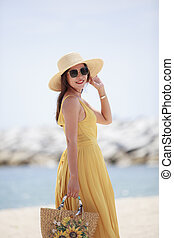 beautiful woman wearing yellow dress standing with happiness smiling at sea side