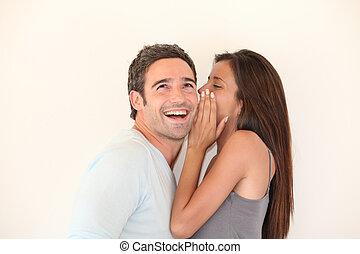 Beautiful woman whispering to boyfriend's ear