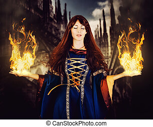 Beautiful woman witch in fantasy medieval dress. Fire magic