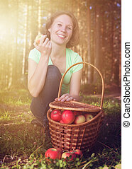 Beautiful woman with a basket full of apples .