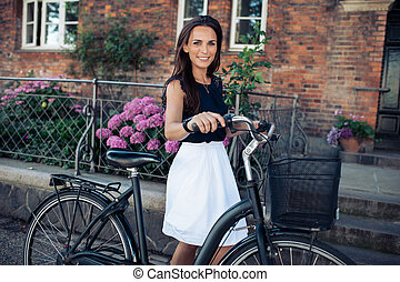 Beautiful woman with a bicycle in city
