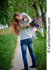 beautiful woman with a bouquet of lupine on the man's shoulder