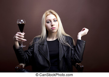 Beautiful woman with a glass of black liquid in hand