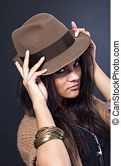 Beautiful woman with a hat on black