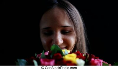Beautiful woman with a large bouquet of flowers in her arms smelling a fragrant colorful roses on black background.