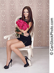 Beautiful woman with a large bouquet of flowers in her arms sitting on chair, modern interior.
