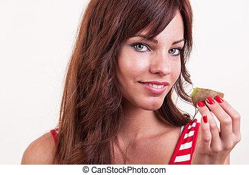 Beautiful woman with a piece of kiwi in her hand - healthy lifestyle