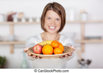 Beautiful woman with a plate of fruits