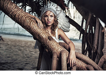 Beautiful woman with a plume leaning against the branch