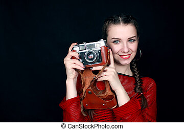 beautiful woman with a retro camera on a black background