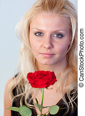 Beautiful woman with a rose with focus on woman