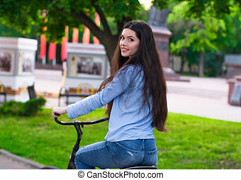 Beautiful woman with a vintage bicycle in a city park