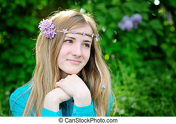Beautiful woman with a wreath of lilac color walks in the park