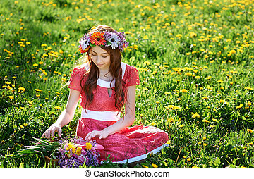beautiful woman with a wreath sitting on the grass in a meadow