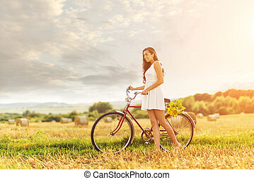 Beautiful woman with an old red bike in a wheat field