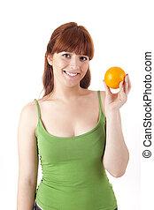 Beautiful woman with an orange fruit