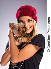 Beautiful woman with autumn fashion, holding yorkshire terrier dog