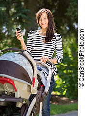 Beautiful Woman With Baby Carriage Using Cell Phone In Park...