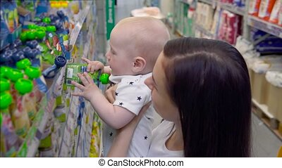 Beautiful woman with baby son shopping in supermarket, young Mother chooses food for their child in the market
