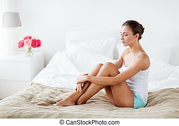 people, beauty, depilation, epilation and bodycare concept - beautiful woman with bare legs sitting on bed at home bedroom