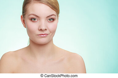 Beautiful woman with bare shoulders. Attractive girl with perfect clean skin. Studio shon on blue green background