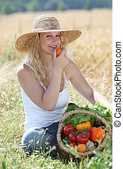 Beautiful woman with basket of vegetables in wheat field