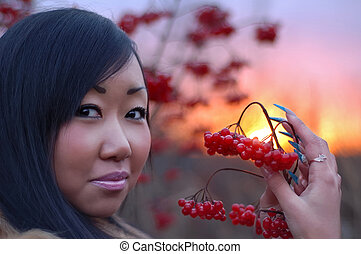 Beautiful woman with berry in her hand