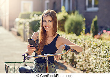 Beautiful woman with bicycle and smartphone