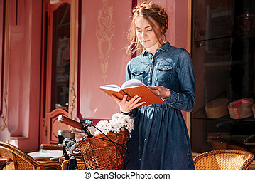 Beautiful woman with bicycle reading a book outdoors