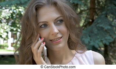 Beautiful woman with big gray eyes talking on the phone close-up