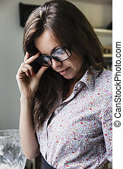 Beautiful woman with black glasses looking at something