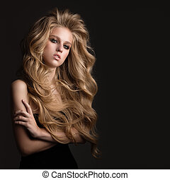Beautiful woman with blond curly hair. Hairstyle.