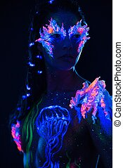 Beautiful woman with body art glowing in ultraviolet light