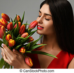 Beautiful woman with bouquet of tulip flowers in red dress