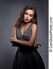 Beautiful woman with bright makeup and long hair, pink lipstick and long curly hairstyle posing in striped dress on grey dark background