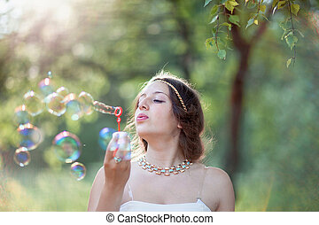 Beautiful woman with bubble blower