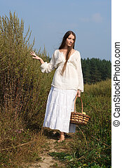 beautiful woman with busket at the summer field