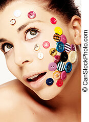 Beautiful woman with buttons on her face