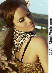 beautiful young woman with long brown hair wearing leopard print dress and cat eye fashion make-up with false lashes, shot outdoors in the middle of the day for saturated summer look.