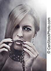 Beautiful Woman with chain in her mouth. Make up and...