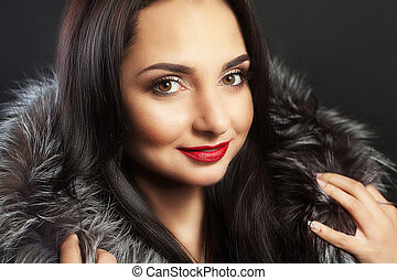 Beautiful woman with clean fresh skin. In winter fur coat. Beautiful smile. Red lipstick On a black background.