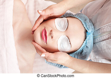 Beautiful woman with clear skin getting beauty treatment - massage of her face at salon