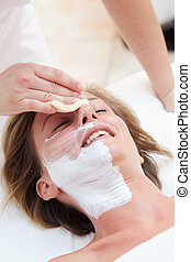 Beautiful woman with clear skin getting facial mask at salon