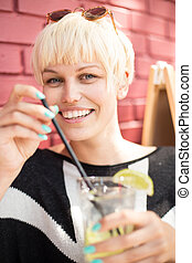 Beautiful Woman with cocktail in cafe. Summer. Outdoor portrait