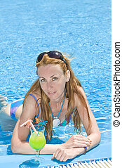 Beautiful woman with cocktail in pool.