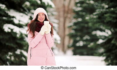 Beautiful woman with coffee to go outdoors on beautiful winter snow day