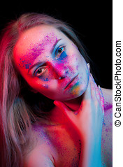 Beautiful woman with color powder on face