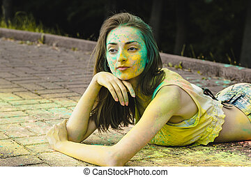 Beautiful woman with colored powder around her